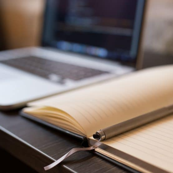 Blurry photograph of notebook in the foreground and computer in the background
